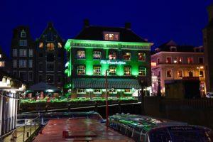 Grasshopper Gebäude bei Nacht grün angestrahlt mit Gracht und Barkasse im Vordergrund